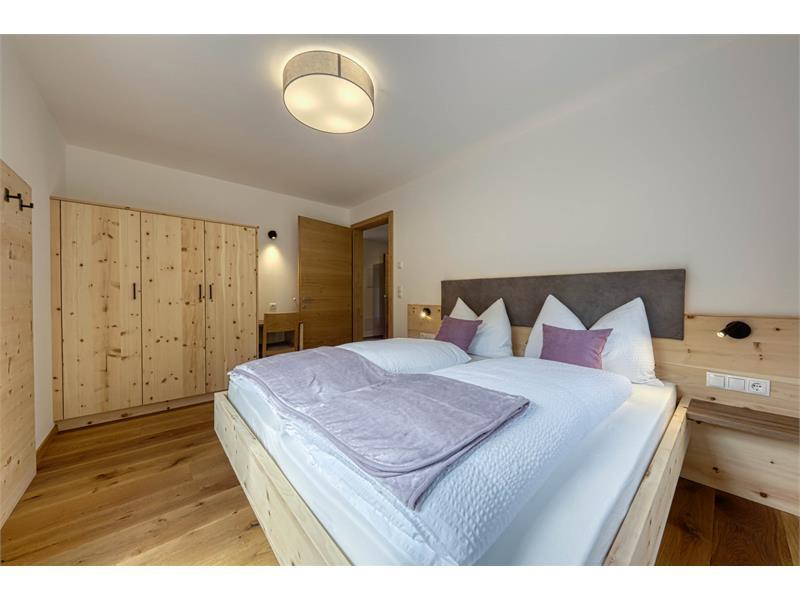 Doppelbettzimmer mit Holzboden, Massivholzmöbel und Blick auf das Etschtal