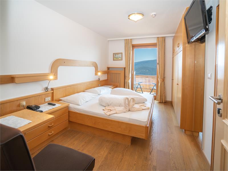 Camera doppia con pavimento in legno o moquette e balcone