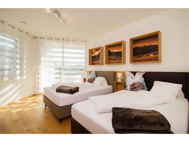 Die Schlafzimmer sind sehr warm und modern eingerichtet. Dieses Zimmer hat 2 französiche Betten