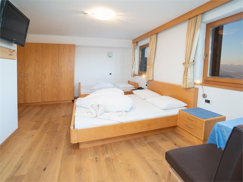 Camera tripla con pavimento in legno o moquette e balcone