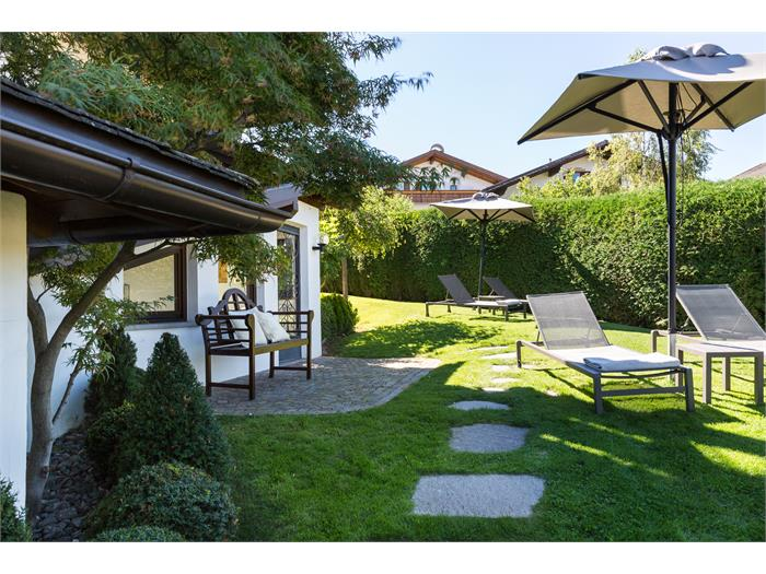 Garden with sunbeds and umbrella in the external building Residence Mayr