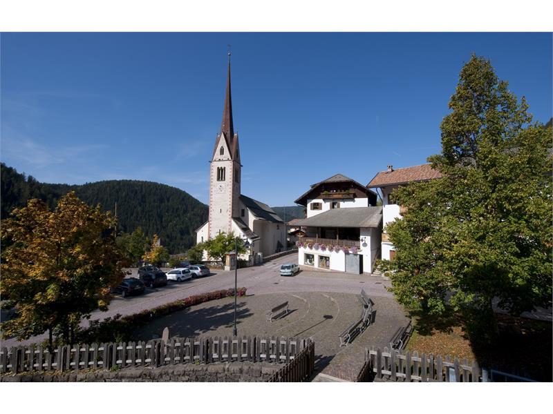 Village square with parish church in Ega