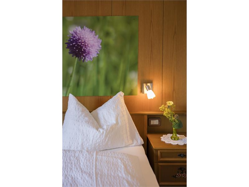 bed with night small box and flowers