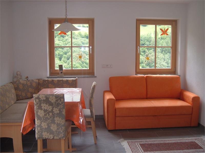 Wohnküche mit Essecke und Sofa