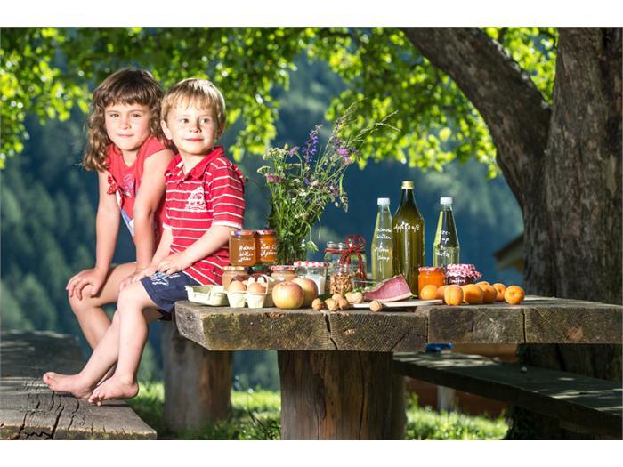 Johanna und Silas unterm Apfelbaum mit einer Auswahl unserer Hofprodukte