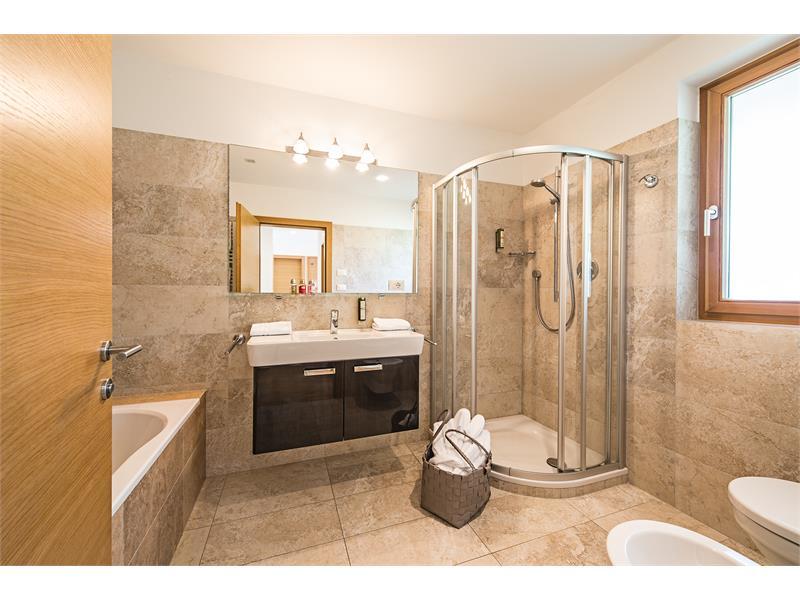 bathroom with tub, shower, toilet, bidet