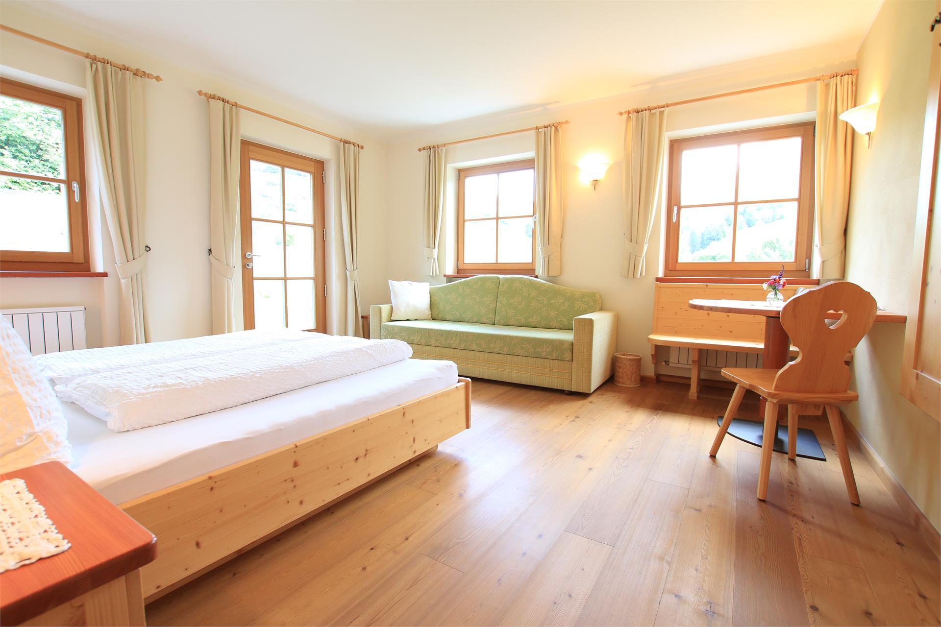 Doppelzimmer mit Massivholzmöbeln und Holzboden sowie Blick nach Süden