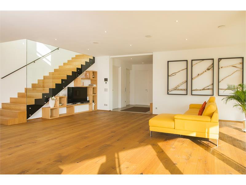 Einsicht in den Ess- Wohnraum mit klaren Linien und wunderschöner sehr breiten Treppe