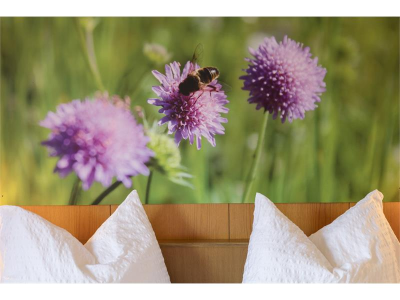 widow's flowers with bee on the bed wall