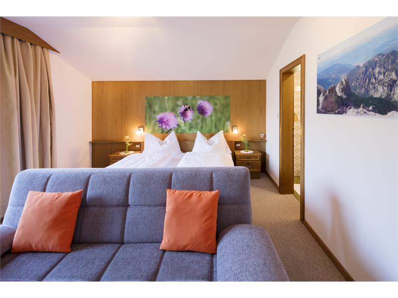 bedroom with sofa and home-made pictures